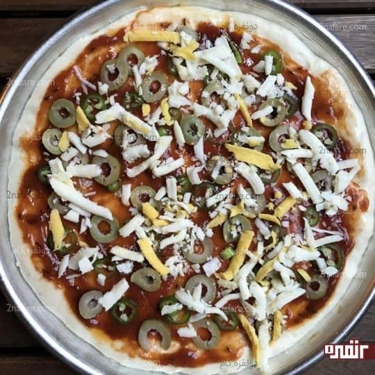 ریختن مواد روی سطح پیتزا