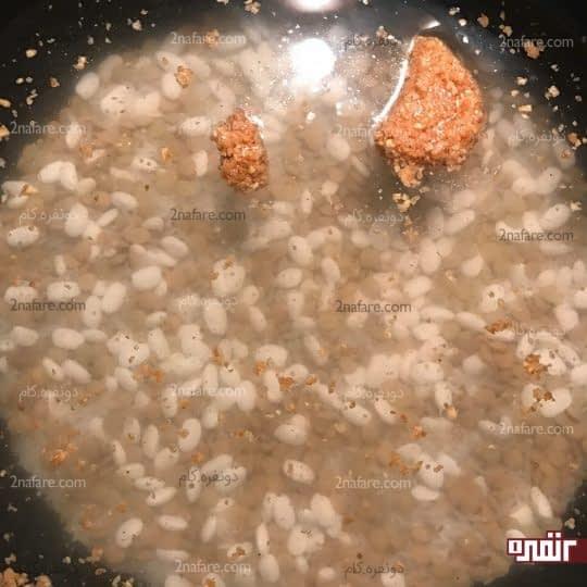 ریختن حبوبات در قابلمه برای پخت