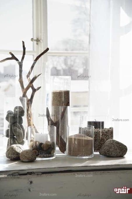 ظروف شیشه ای پر شده با سنگریزه ها و شن های ساحلی
