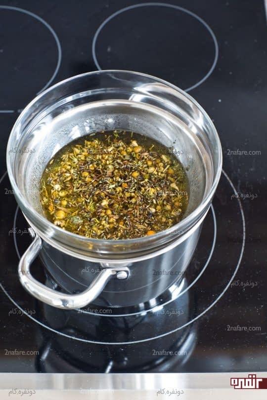 قرار دادن مخلوط گیاهان و روغن روی بخار آب