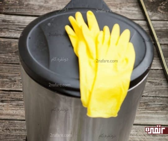 پوشیدن دستکش برای تمیز کردن سطل زباله
