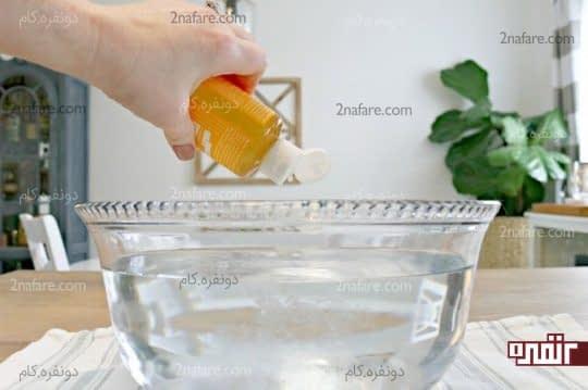 ریختن دو قاشق غذاخوری صابون کاستیل درون کاسه آب گرم