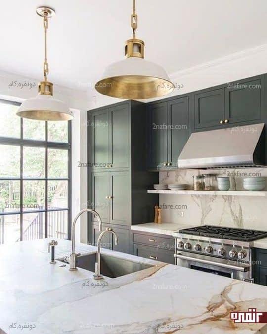 آشپزخانه ای با لوازم استیل و لوسترهای طلایی رنگ