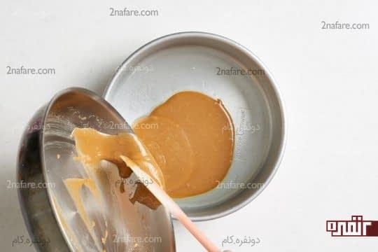 ریختن مخلوط کره و شکر در قالب کیک