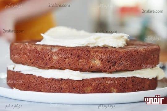 قرار دادن دو لایه کیک روی هم و پوشاندن آنها با کرم پنیری