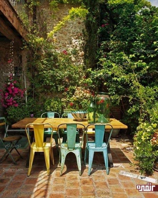 میزغذاخوری چوبی و صندلی های فلزی در حیاط خلوت