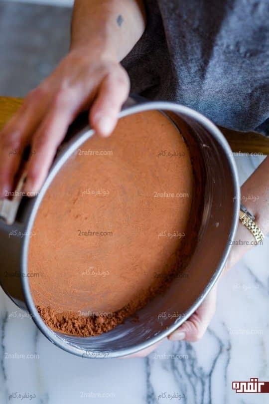 پخش کردن پودر کاکائو کف قالب کیک