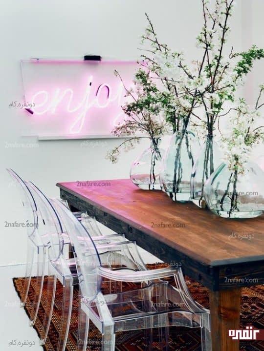 کنتراست بین میز چوبی غذاخوری با صندلی ها، اکسسوری های شیشه ای و نوار نئونی صورتی رنگ
