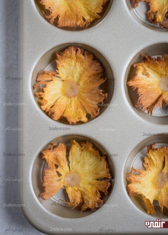 گذاشتن برش های آناناس در قالب مافین
