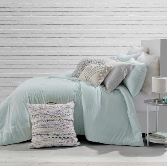احساس آرامش در اتاق خواب خاکستری با روتختی های لطیف به رنگ سبزنعنایی