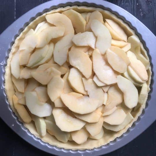 ریختن سیب های خرد شده روی خمیر پای